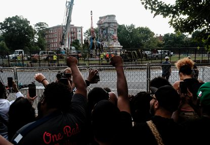 Onlookers cheer as the statue of Robert E. Lee is removed from its pedestal in Richmond, Va., on Wednesday morning, Sept. 8, 2021. The Confederate memorial was erected in 1890, the first of six monuments that became symbols of white power along the main boulevard in Richmond. (Michael A. McCoy/New York Times)