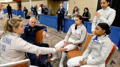 USA Team coach Edward Korfanty, second from left, listens as USA's Dagmara Wozniak, left, talks strategy with teammates Monica Aksamit, center, Zara Moss, standing, and Kamali Thompson, seated at right, at the Women's Sabre World Cup at the Baltimore Convention Center.
