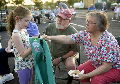 Christina Bain, 9, of Girl Scout Troop 1698 shows of some of the pins on her vest to Carroll Lutheran Village residents Dan and Pam Short as her troop pays a visit to the community to roast marshmallows and sing campfire songs Wednesday, Oct. 2, 2019.