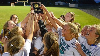 Members of the Patterson Mill girls lacrosse team celebrate with the region championship plaque won Wednesday night.