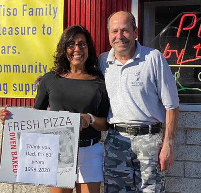 Deanna Penyak, left, and her brother, Michael Tiso, pose in front of Mike's Pizza House, which was opened in 1959 by their father, Mike Tiso. The shop is scheduled to close on Sept. 12.