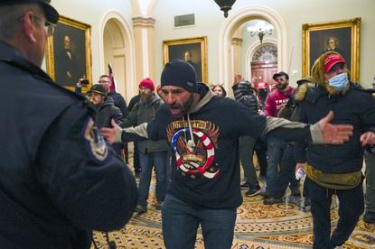 In this Jan. 6, 2021, file photo, Trump supporters gesture to U.S. Capitol Police in the hallway outside of the Senate chamber at the Capitol in Washington. Doug Jensen, an Iowa man at center, was jailed early Saturday, Jan. 9, 2021 on federal charges, including trespassing and disorderly conduct counts, for his alleged role in the Capitol riot. (AP Photo/Manuel Balce Ceneta, File)
