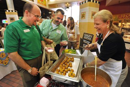 "Bill Connor, left, and Vince McPhail of JHU talk with Damye Hahn of Faidley's as they try samples. Local food vendors presented their products to buyers from hotels, hospitals, colleges and other institutions at a ""Made in Baltimore"" fair in 2018."
