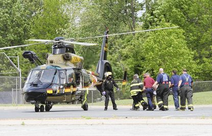 Fire and rescue crews take Michael Euler Sr., of Fallston, to a waiting Medevac following Tuesday's three vehicle accident in Fallston that killed two people and injured Euler and a fourth person.