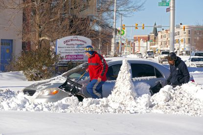 Two people move about their car, which is stuck on Eutaw Place at North Ave. on the morning after a powerful snowstorm hammered the region.