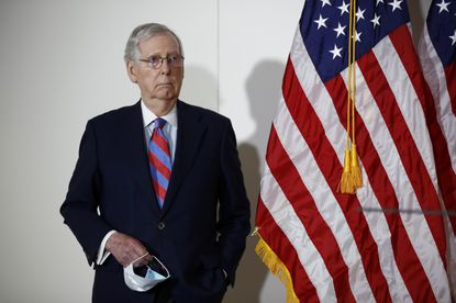 Senate Majority Leader Mitch McConnell of Kentucky holds a face mask used to protect against the spread of the new coronavirus as he attends a news conference on Capitol Hill in Washington.