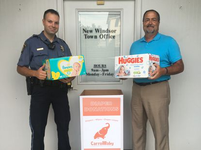 Mayor Neal Roop and Master Deputy Brian Colussy host a CarrollBaby bin at the New Windsor Town Hall.