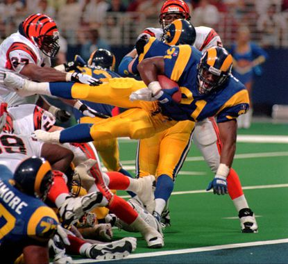 Former St. Louis Rams running back Lawrence Phillips (21) leaps over a mound of players as he scores his second touchdown of the day during the fourth quarter against the Cincinnati Bengals on Sunday, Sept. 1, 1996, in St. Louis, Mo.Phillips was found dead in his jail cell in California on Jan. 13, 2016.