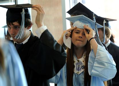 Michael Wack, left, and Maddy Walsh adjust their caps as they file into the Gill Center before Westminster High School's 114th Annual Graduation Exercises at McDaniel College in Westminster Sunday, June 8, 2014.