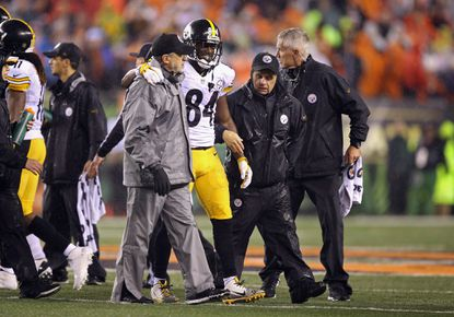 Antonio Brown of the Steelers is helped off the field by training staff in the fourth quarter against the Bengals during the AFC Wild Card Playoff game last Saturday.