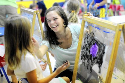 Serra Berry, center, works with Catie Ash, 6, as she paints at Berry Patch Early Learning Center in Hampstead Friday, Sept. 5.