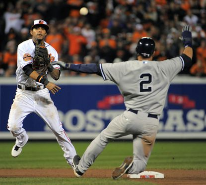 Baltimore Orioles second baseman Robert Andino (11) throws over New York Yankees shortstop Derek Jeter (2) but the relay fails to get Ichiro Suzuki in the seventh inning of Game 2 of the ALDS Championship Series at Oriole Park at Camden Yards.