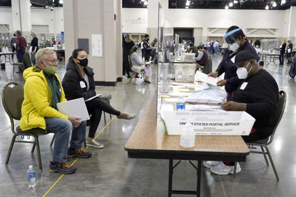 Election workers, right, verify ballots as recount observers, left, watch during a Milwaukee hand recount of presidential votes at the Wisconsin Center, Friday, Nov. 20, 2020, in Milwaukee. The recount of the presidential election in Wisconsin's two most heavily Democratic counties began Friday with President Donald Trump's campaign seeking to discard tens of thousands of absentee ballots that it alleged should not have been counted. (AP Photo/Nam Y. Huh)