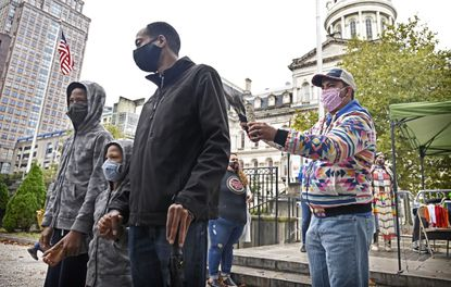 """Sgt. Andrew Thompson (Ret. US Army), right, burns sage to """"bless"""" Councilman John Bullock, center, and his sons Thomas, 11, left, and George, 5, as about 30 people gather outside Baltimore City Hall to call for Mayor Bernard C. """"Jack"""" Young to sign bill to replace Columbus Day with Indigenous Peoples Day. Bullock is the sponsor of the bill this year."""