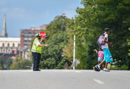 A young student waves back at the crossing guard after getting out of school early at Johnston Square Elementary School due to the heat and the lack of air conditioning in the building.