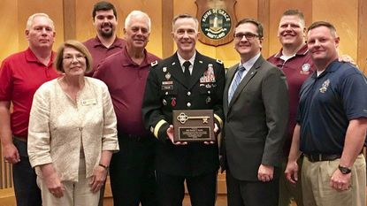 Aberdeen Proving Ground senior commander Maj. Gen. Randy Taylor and his husband, Lucas, center, pose with Havre de Grace Mayor William T. Martin, right, and members of the City Council Monday. Martin gave Taylor, who departs for a new assignment in late June, a key to the city.