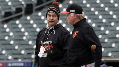 Orioles executive vice president Dan Duquette, left, and manager Buck Showalter talk during a practice at the American League Division Series in October.
