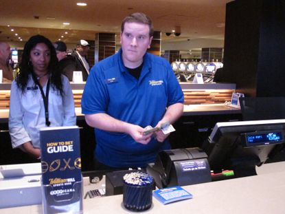 In this March 8, 2019 photo, a clerk counts money wagered by a customer at the sports betting lounge at the Tropicana casino in Atlantic City N.J. On Sept. 14, 2020, New Jersey gambling regulators announced that New Jersey set a new national record for the amount wagered on sports in a single month in the U.S. with nearly $668 million bet on games. (AP Photo/Wayne Parry)