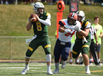 McDaniel's Tyler Palermiti looks to pass as Gettysburg's Alex Raimondo gets past receiver Donovan Taylor during a Centennial Conference football game at McDaniel College on Saturday, September 28.