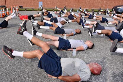The 1904 class of Baltimore police officer trainees go through a morning exercise routine, including leg lifts, push-ups and sit-ups, as they begin their police academy training.