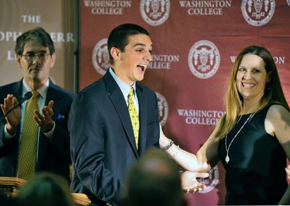 Tim Marcin (center) this year's winner of the Sophie Kerr Prize, is greeted by Kathryn Moncrief, chair of the Department of English at Washington College. Applauding on the left is Michael Dirda, a book critic at The Washington Post.