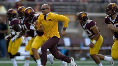 P.J. Fleck of the Minnesota Golden Gophers runs with his players during warmups before the game against the Miami (Ohio) Redhawks on Sept. 15, 2018 at TCF Bank Stadium in Minneapolis, Minnesota.