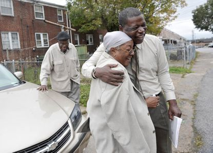 Baltimore City Councilman Warren Branch wraps up a visit to William and Myrtle Kelly with a hug in an alley behind their home. The Kellys, who have known Branch for years, talked with him about the alley, which needs resurfacing.
