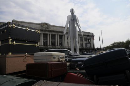 """Jonathan Borofsky's """"Male/Female"""" statue surveys luggage at Baltimore's Penn Station. The public art piece has proven to be a divisive landmark since it was installed in 2004. (Gabriella Demczuk/Baltimore Sun)."""