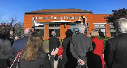 DYLAN SLAGLE/STAFF PHOTOA sign naming the Hill Family Center is unveiled during a ceremony to recognize major improvements to the Y of Central Maryland's facility in Westminster Tuesday, November 8, 2011.