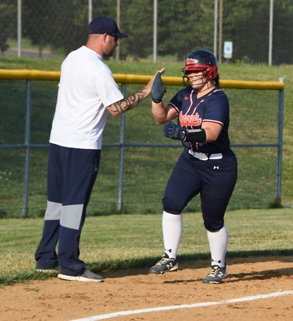 Reservoir #25, Kayla Ecker high-fives Asst. Coach, David Burke as she rounds 3rd after hitting a home run in the 5th inning. Softball game between two top teams in the county, Reservoir and Wilde Lake Tuesday May 25, 2021. Reservoir defeated Wild Lake in 5 innings, 15-1.