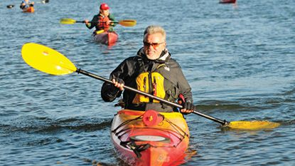 Mike Appleby of Columbia paddles to shore, followed by Steve Hayleck of Dayton. The meeting location varies. On this night, about 20 kayakers met at Triadelphia Reservoir in Dayton.