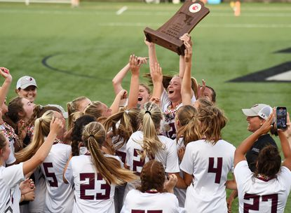 Broadneck's Alexis Abe hoists the championship trophy surrounded by the rest of the team. The Broadneck Bruins defeated the Arundel Wildcats for the MPSSAA Girls Lacrosse Class 4A State Championship, Saturday, June 19, 2021, at Loyola's Ridley Athletic Complex.