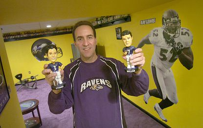 Bruce Raffel holds up his Matt Stover (left) and Kyle Boller bobbleheads while posing in his basement, which has purple carpeting and yellow walls as a tribute to the Ravens.