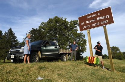 From left, Jan Stambaugh, Dave Lease and Evan Staley attach a wreath to a new sign dedicating a portion of Md. 75 in memory of Army Private Russell Milberry of Union Bridge, who was killed in Vietnam in 1968.