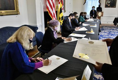 Corynne B. Courpas, treasurer of the Carroll County Democratic Central Committee, front, Thelma T. Daley, second from left, and other electors sign the Certificate of Vote during the 59th meeting of the Maryland Electoral College at the State House. Dec. 14, 2020.