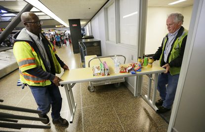 Port of Seattle workers Aaron Washington, left, and Tracy Jenkins, right, carry a table and snacks into a room near where passengers arrive on international flights at Seattle-Tacoma International Airport, onFeb. 28, 2017, in Seattle.