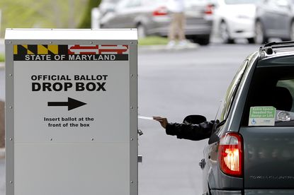 In this Tuesday, April 28, 2020, file photo, a motorist drops off a mail-in ballot outside of a voting center during the 7th Congressional District special election, in Windsor Mill.