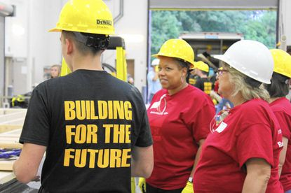 A Harford Tech student helps Bank of America Vice President Janet Currie in building a Habitat home at the school.