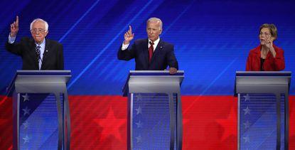 Democratic presidential candidates Sen. Bernie Sanders (I-VT), former Vice President Joe Biden, and Sen. Elizabeth Warren (D-MA) raise their hands during a Democratic in Texas on Sept. 12, 2019.