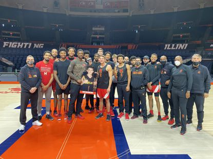The Maryland men's basketball team poses for a picture with a cutout of Ben Snyder, a 9-year-old signed to the program through Team IMPACT. Team IMPACT is an organization that pairs children facing serious and chronic illnesses with college programs.