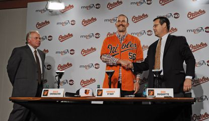 Orioles executive vice president Dan Duquette, right, shakes hand with relief pitcher Darren O'Day as manager Buck Showalter, left, looks on during a news conference at Camden Yards.