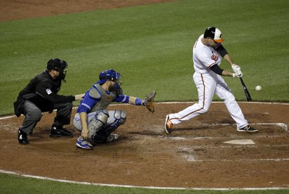 Orioles' J.J. Hardy, right, hits a sacrifice fly ball in front of Toronto Blue Jays catcher Russell Martin and home plate umpire Dan Bellino during the seventh inning in Baltimore, Thursday, April 21, 2016.