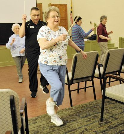 """JoAnn Strickler followed by Bob Hunter, activities director, conducts as they march through the great hall at Glen Meadows Retirement Community. Members gather for a workout called Music 'N Motion. Hunter leads them in """"conducting"""" classical music."""