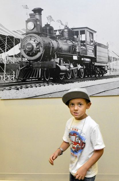 Luke Curlett, 6, of Arbutus, passes by a 1927 photo from The Fair of the Iron Horse, staged by the B&O Railroad, near the entrance to the library.