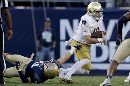 Navy had trouble stopping quarterback Ian Book and Notre Dame last season in San Diego. Here, Book escapes the tackle attempt of outside linebacker Evan Fochtman during the the 2018 meeting, which the Fighting Irish won 44-22. (AP Photo/Gregory Bull)