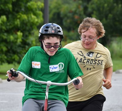 Camper Tyler Stevenson shows a big smile as he makes the turn and picks up some speed while volunteer Alex Stewart tries to keep up as they speed around the course outside during the Harford Bike Camp at the Churchville Parks and Recreation complex Wednesday, July 14, 2021.