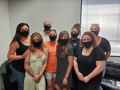 The employees of the Thirty Hair salon in Columbia pose with masks on.