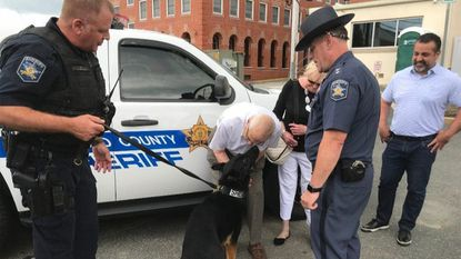 Louis Storm gets some love from Harford County Sheriff's Office police dog Diogi as a thank you for Storm's donation that will allow the Sheriff's Office to buy two pop-and-lock systems to ensure the agency's police dogs' safety in their vehicles.
