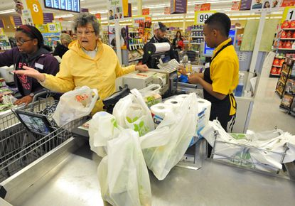 Betty Reynolds buys groceries from cashier DeAndre Honeyblue, right, at the Giant grocery store on 41st Street in Baltimore in 2014. File.