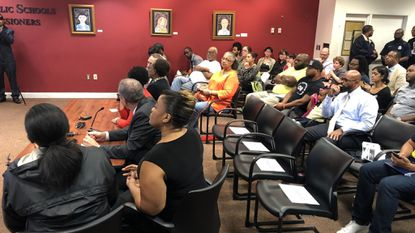 People packed the Baltimore school system headquarters Thursday for a forum on whether to arm school police.